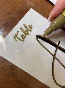 テーブルナンバーの文字を金の油性ペンでなぞる