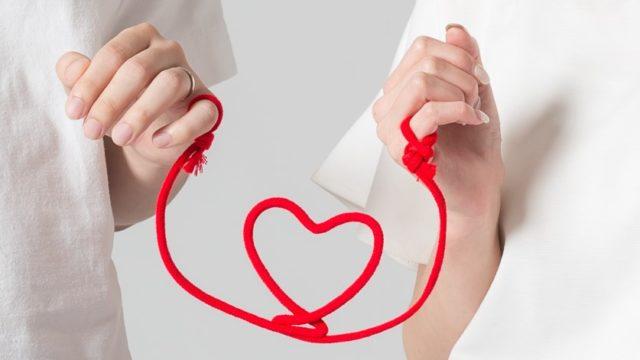 男女が赤いハートの糸を手に持っている